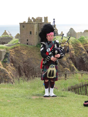 dunnottar castle: Lone piper in front of Dunnottar Castle, near Stonehaven, Scotland Editorial