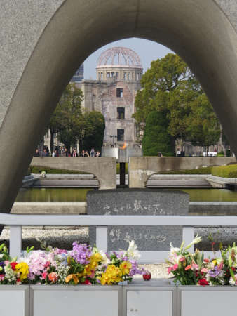 View taken at the Hiroshima peace memorial, with the peace flame in the middleground and the Atomic Dome in the background