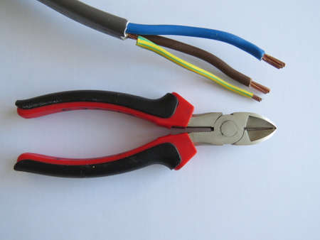 handtool: Pair of side cutters next to some electrical cable.