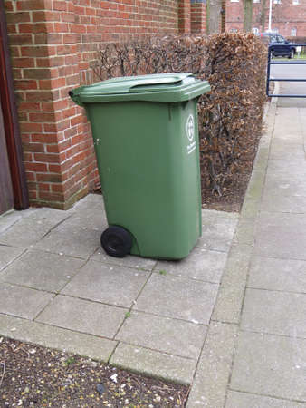 wheelie: Green recycling bin on the pavement awaiting emptying. Stock Photo