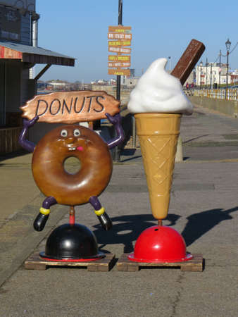 southsea: Signs advertising doughnuts and ice cream for sale on the promenade of Southsea seafront.