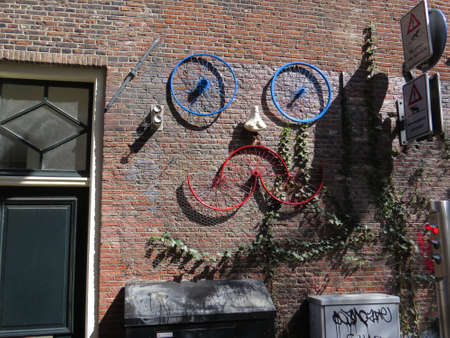 humourous: Face made from old bicycle wheels on wall in Amsterdam.