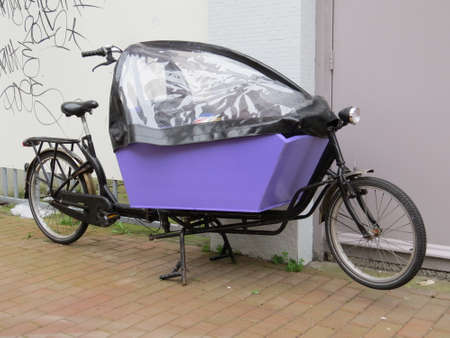 quite: Bicycle with a covered compartment for transporting goods. These are quite common in the Netherlands.