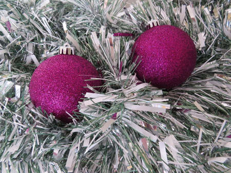the tinsel: Christmas tree decorations amongst some tinsel.