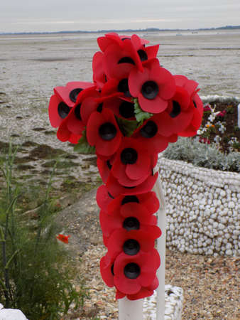 Cross made from paper poppies. The poppy has been used for many years as a symbol of remembrance of the people who have died during conflicts throughout the world. photo