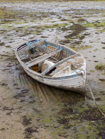 disrepair: Old neglected boat stranded at low tide in Langstone harbour Portsmouth UK.