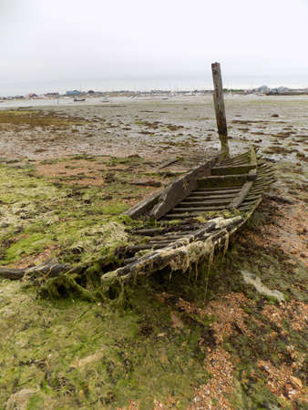 purely: Remnants of an old boat in Langstone harbour Portsmouth UK. This boat was beyond economical repair several years ago. During this time it has gone from a complete vessel to what is left today purely due to the destructive action of the tide.