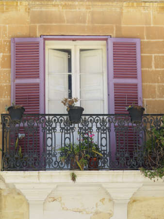 balcony window: Window surrounded by wooden shutters on a balcony in the walled city of Mdina in Malta.