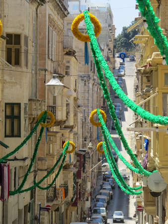 occur: Valletta street decorated in preperation for one of the many fiestas that occur throughout the year. Stock Photo