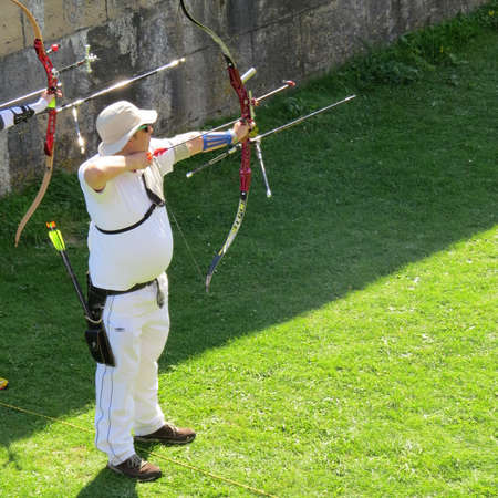 bowman: Archer about to release an arrow during a competition. Stock Photo