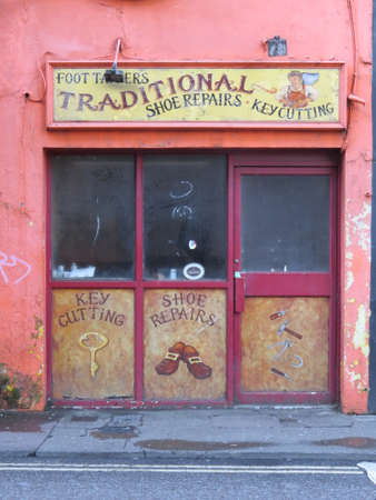 repairer: Cork, Ireland - July 19th, 2015: View of a shop front of a long gone shoe repairers - another victim of recession in the country.