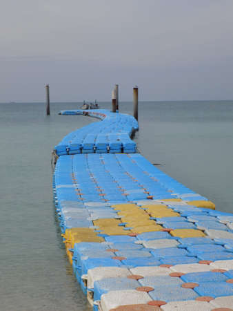 floats: Pontoon made from plastic floats used to access small boats from a beach on Koh Larn Island in Thailand.