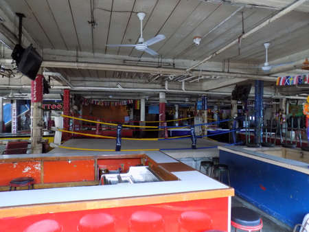 cater: Pattaya, Thailand - November 3rd, 2015: Collection of open beer bars grouped around a Thai boxing ring. These bars cater primarily for tourists and put on Thai boxing exhibitions on a nightly basis.