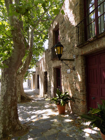 Faade of a building in a shady street in the town of Colonia de Sacramento, Uruguay. Imagens