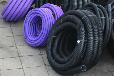 plastic conduit: Rolls of plastic conduit awaiting installation in a construction site trench.