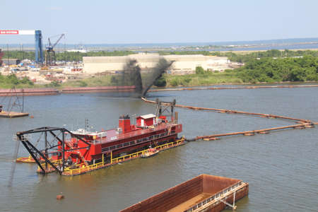 silt: Mobile, USA - May 24th, 2016: Whilst dredging the harbour at Mobile, Alabama, the pipe back to shore ruptured throwing black silt all over the surface of the water.