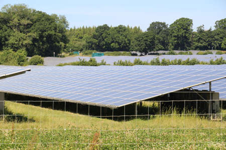 steadily: Solar panels in a field. The use of these to generate renewable energy has been steadily increasing throughout the UK.