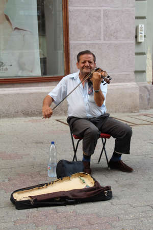 Pecs, Hungary - 9 August, 2017: Violinist busking on the streets of Pecs, Hungary.
