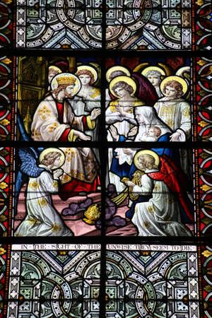 Janela de vitral na catedral de Salisbúria. Um dos muitos retratando imagens de santos, ícones religiosos e afins. Foto de archivo - 94951260