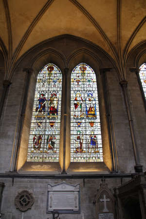 Janela de vitral na catedral de Salisbúria. Um dos muitos retratando imagens de santos, ícones religiosos e afins. Foto de archivo - 94951382