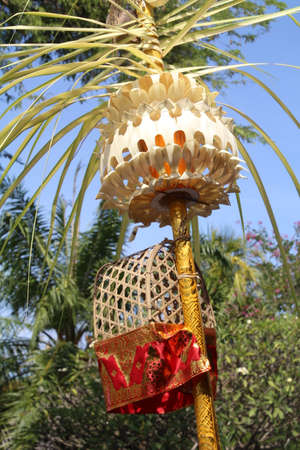 Balinese festival decoration. These are displayed outside homes and businesses and consist of a bamboo pole which is decorated with a small shrine and ornamentation made from dried palm leaves.