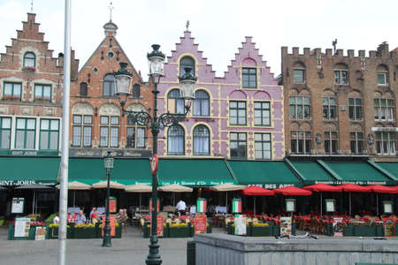 Bruges, Belgium - 15 June, 2018: Restaurants in Market Square. There are many such places to eat all around the square and the surrounding architecture can be admired whilst taking a break from sightseeing.