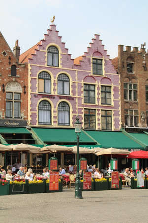 Bruges, Belgium - 19 June, 2018: Restaurants in Market Square. There are many such places to eat all around the square and the surrounding architecture can be admired whilst taking a break from sightseeing.