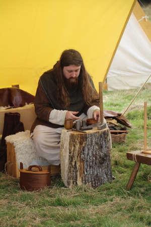 Battle, UK - 14 October, 2018: Man in saxon period clothing demonstrating how to make hammered coinage at a Battle of Hastings reenactment weekend. Editorial