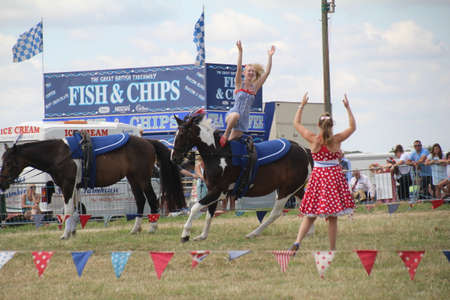 Southampton, UK - 28 July, 2019: The horsewomen 'Galloping Acrobats' performing tricks on horseback for the enjoyment of the crowd at Netley Steam and Craft Show. Banco de Imagens - 127946543