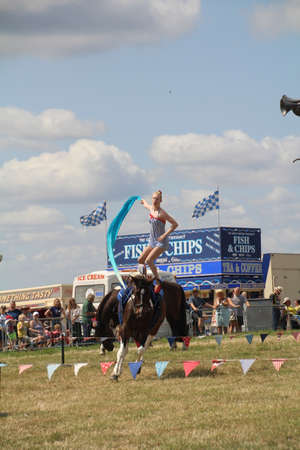 Southampton, UK - 28 July, 2019: The horsewomen 'Galloping Acrobats' performing tricks on horseback for the enjoyment of the crowd at Netley Steam and Craft Show. Banco de Imagens - 127946544