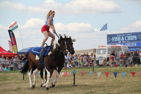 Southampton, UK - 28 July, 2019: The horsewomen 'Galloping Acrobats' performing tricks on horseback for the enjoyment of the crowd at Netley Steam and Craft Show. Banco de Imagens - 127946563