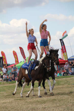 Southampton, UK - 28 July, 2019: The horsewomen 'Galloping Acrobats' performing tricks on horseback for the enjoyment of the crowd at Netley Steam and Craft Show. Banco de Imagens - 127946565