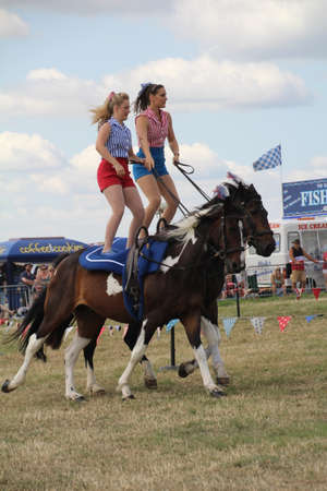 Southampton, UK - 28 July, 2019: The horsewomen Galloping Acrobats performing tricks on horseback for the enjoyment of the crowd at Netley Steam and Craft Show. Editorial