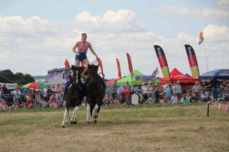 Southampton, UK - 28 July, 2019: The horsewomen 'Galloping Acrobats' performing tricks on horseback for the enjoyment of the crowd at Netley Steam and Craft Show. Banco de Imagens - 127946567
