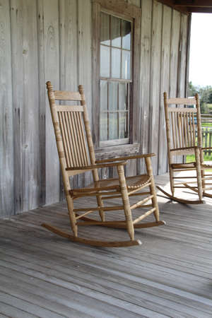 Rocking chair on the veranda of a wooden shack. Banco de Imagens