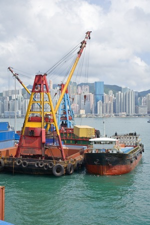 Container being swung from lighter to dockside by large derrick. High density apartments of Hong Kong Island in background. Stock Photo