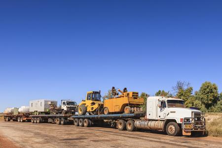 オーストラリアの北部準州のアウトバックでロードトレインは、休憩所で、道路建設機器を運ぶ。ロードローラー、キャラバン、トラック、水と燃