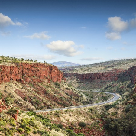 Magnificent red cliffs tower above a lonely road in the Pilbara region of Western Australia