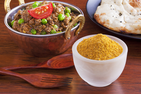 Curry powder with a beef mince curry, keema matar with peas, and naan bread.