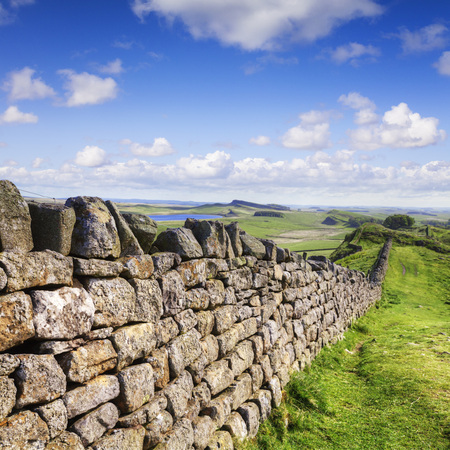 Dry stone wall running the same course as Hadrian's Wall in Northumberland, and probably making use of stones recycled from the wall. Stock Photo