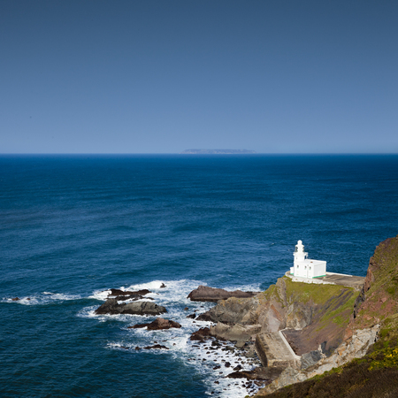 The lighthouse at Hartland Point, on the north coast of Devon, England. Lundy Island, in the Bristol Channel is visible in the distance.
