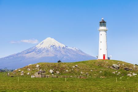Cape Egmont Lighthouse and Taranaki, or Mount Egmont, in the Taranaki Region of New Zealand Archivio Fotografico