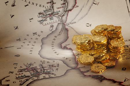 Doubloons and Treasure Map - Vecchia mappa di Atlantide e una pila di dobloni d'oro. Archivio Fotografico - 94276283