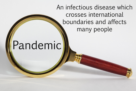 Pandemic Concept with Words and Magnifying Glass Stock Photo