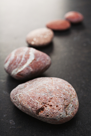 Curving Line of Red and Grey Pebbles on Dark Background