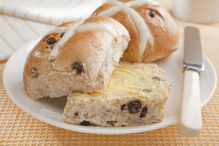 Buttered hot cross buns on yellow cloth