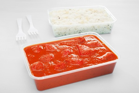 A plastic takeaway container with chicken tikka masala on a blue background, and with pilau rice and forks. Stock Photo
