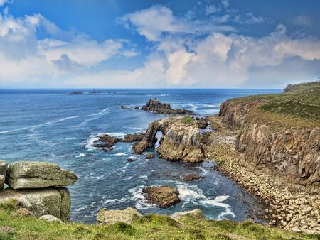 Rocky coastline of Lands End, Cornwall, UK, with the arch, Enys Dodnan, and the rock formation The Armed Knight, with the Longships Lighthouse offshore. 版權商用圖片