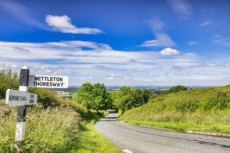 Lincolnshire Wolds, UK, with Country Road and Signpost 版權商用圖片