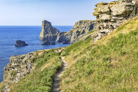 The South West Coast Path in a beautiful stretch of the Cornish coast, between Tintagel and Bossiney, with cliffs and offshore rocks, on a beautiful summer day.